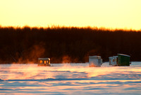Vapor coming out of the lake where it's not completely frozen, while ice fishing huts are already installed on the lake.