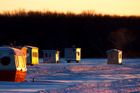 Ice fishing huts reflecting the sun giving a pink color to the snow.