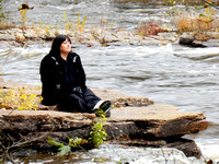 Native American woman sitting on a rock near the rapids