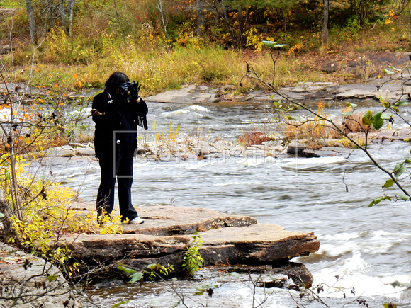 Native American woman taking picture of rapids in the middle of the woods