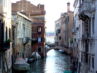 Scenery of a narrow canal in Venice with boats parked by the buildings